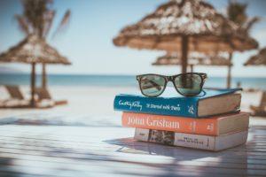 Strandmiljö med böcker och solglasögon